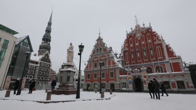 Pedestrians pass the House of Blackheads and a statue of Roland onTown Hall square in the old town in Riga Latvia on Sunday Jan 8 The National...