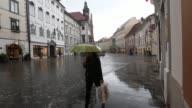 Pedestrians pass through a shopping street in the centre of Ljubljana many holding umbrellas Ljubljana city centre in the rain on May 06 2013 in...