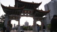 Pedestrians pass under a traditional Chinese gate.
