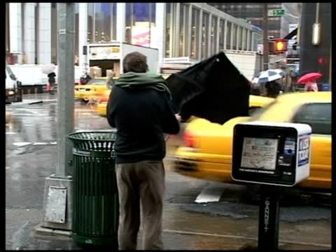 Pedestrians struggle with broken umbrellas in high winds Manhattan New York