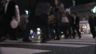 Pedestrians use a crosswalk in front of Tokyo's Shinagawa Railway Station.