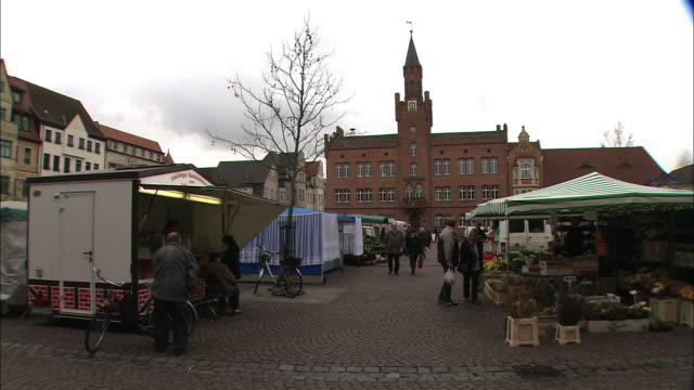 Pedestrians visit shops at a market in Bitterfeld-Wolfen, Germany.