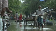 Pedestrians wade along a flooded street. Available in HD.