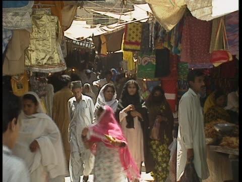 Pedestrians walk along a busy market in Rawalpindi Pakistan