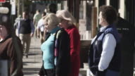 Pedestrians walk along a sidewalk in Charleston.