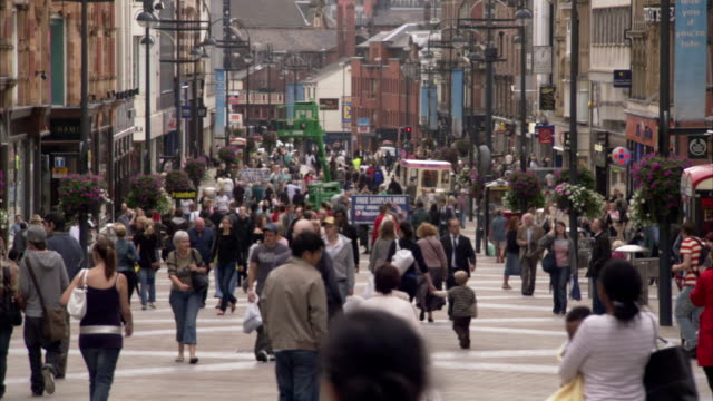 Pedestrians walk along Briggate in the Victoria Quarter in Leeds, England. Available in HD.