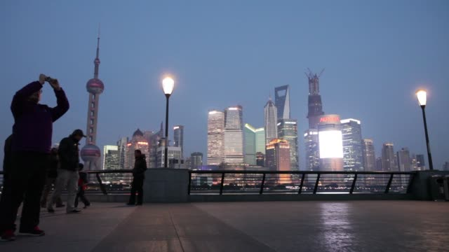 Pedestrians walk along the Bund commercial buildings and skyscrapers on skyline in the Pudong area at night in Shanghai Pedestrians walk along Bund...
