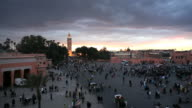 Pedestrians walk along the Djemaa el-Fna night market in Marrakesh at dusk.