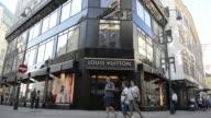 Pedestrians walk down a high street in Vienna Austria on Wednesday Aug 26 2015 Shots Pedestrians walk past a Louis Vuitton store operated by LVMH...