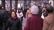 Pedestrians walk down a sidewalk lined with trees.