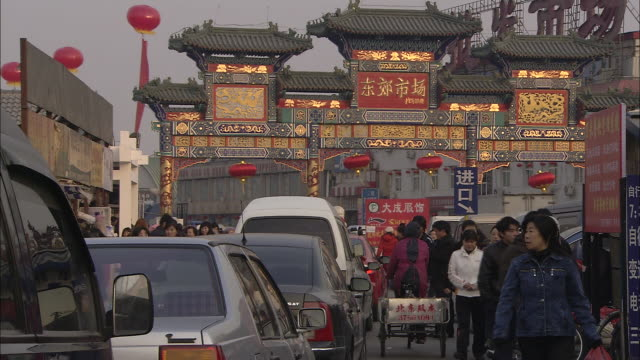 Pedestrians walk in front of traffic on a street decorated for the Chinese New Year.