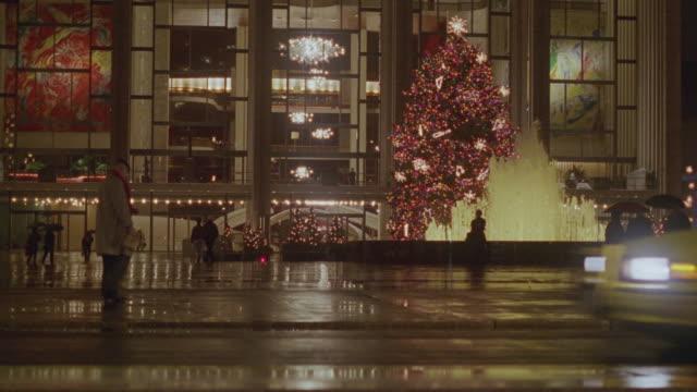 Pedestrians walk near a fountain and Christmas tree.