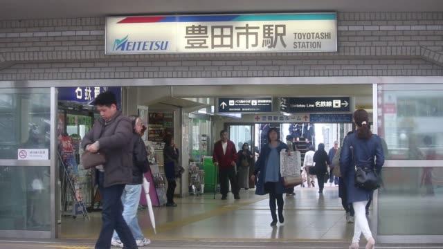 Pedestrians walk near Toyota City station in Toyota City Aichi Prefecture Japan on Sunday March 29 A sign of Toyota City station WS pan LR of train...