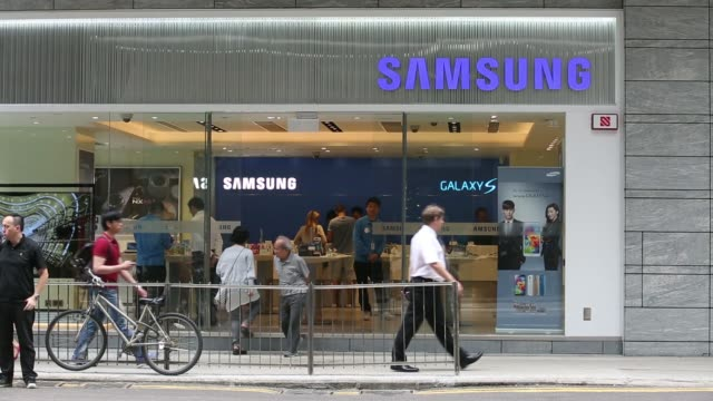 Pedestrians walk past a bus in front of a Samsung Electronics Co Galaxy S5 smartphone advertisement outside a Samsung retail store in the Central...