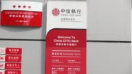 Pedestrians walk past a China Citic Bank Corp branch in Shanghai China on Tuesday March 21 Close up logo for China Citic Bank Corp is displayed...