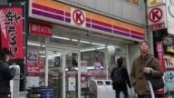 Pedestrians walk past a Circle K convenience store operated by Circle K Sunkus Co a subsidiary of Uny Group Holdings Co in Tokyo Japan on Saturday...