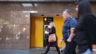 Pedestrians walk past a Commonwealth Bank of Australia branch in Sydney Australia on Monday Aug 7 A customer uses an automated teller machine outside...