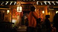 Pedestrians walk past a Lake Houhai tea house hostess.