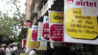 Pedestrians walk past advertisments for Idea Cellular Ltd center and Vodafone India Ltd products and services are displayed outside a mobile phone...