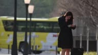 Pedestrians walk past lamp posts in Tokyo Japan on Friday March 31 A woman uses a smartphone as pedestrians walk past Women wearing scarves wait to...