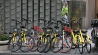 Pedestrians walk past Ofo Inc bicycles and Mobike bicycles parked on a sidewalk in Shanghai China on Thursday May 25 2017