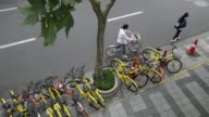 Pedestrians walk past Ofo Inc bicycles and Mobike bicycles parked on a sidewalk in Shanghai China on Thursday May 25 A commuter parks an Ofo Inc...