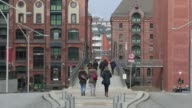 Pedestrians walk past retail outlets in the Uberseequartier district in the HafenCity development in Hamburg Germany on Friday Feb 13 construction in...