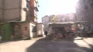 Pedestrians walk past shops and apartment buildings in a Tirana neighborhood. Available in HD.