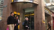 Pedestrians walk past signage for Commonwealth Bank of Australia displayed outside a branch in Sydney Australia on Monday Aug 7 A customer uses an...