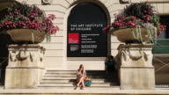 Pedestrians walk past the Art Institute of Chicago on September 17 2014 in Chicago Illinois The museum which draws around15 million visitors a year...