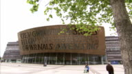 Pedestrians walk past the Cardiff Millennium Centre. Available in HD.