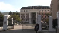 Pedestrians walk past the gate of the Parliament House of South Africa in Cape Town.