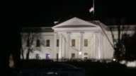 Pedestrians walk past the northern facade of the White House at night in Washington DC US on Monday Dec 7 2015 Photographer Andrew Harrer/Bloomberg...