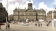 Pedestrians walk past the Royal Palace in Amsterdam. Available in HD.