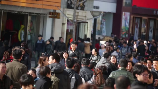 Pedestrians walk through the Wangfujing shopping district of Beijing People walk through the Wangfujing shopping district of Beijing Pedestrians walk...