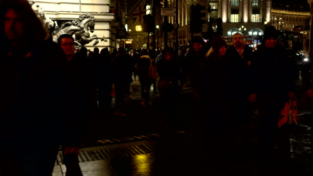 Pedestrians walk towards camera at Piccadilly Circus in London at night in slow motion
