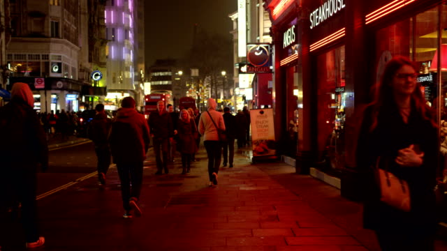 Pedestrians walk towards camera between Piccadilly Circus and Leicester square in London at night in slow motion