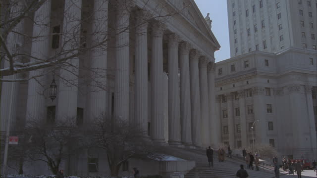 Pedestrians walk up the stairs of the civil branch of the New York Supreme Court Building.