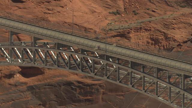 MS AERIAL ZO Pedestrians walking across bridge at Glen Canyon Dam and surrounding landscape / Arizona, United States
