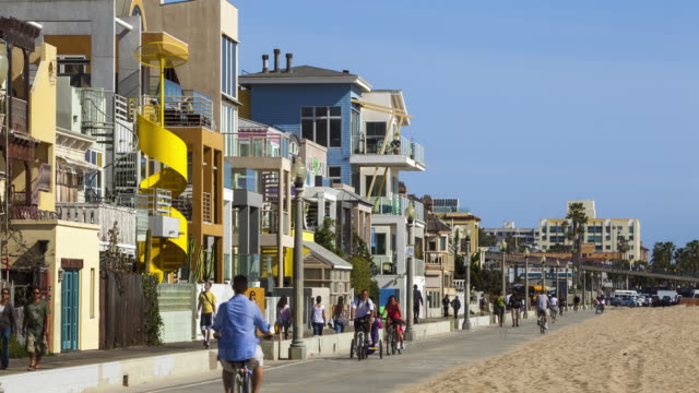 WS Pedestrians walking by and cyclists riding down the boardwalk with modern houses in beachfront / Venice, California, USA