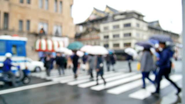 Pedoni camminare in città piovosa. Fuori fuoco sullo sfondo della vivace città con strada di attraversamento persone a Kyoto, Giappone