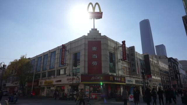 Pedestrians walking past a McDonald's restaurant on a walking street