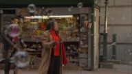 WS Pedestrians walking past news stand while bubbles float in air / Manhattan, New York, USA