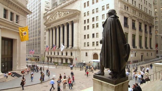 T/L Pedestrians walking past statue of George Washington facing Wall Street / New York, New York, United States