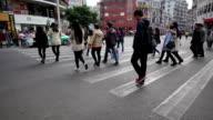 pedestrians walking through crosswalk in modern street of guangzhou