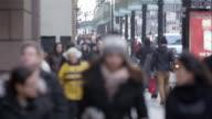 Pedestrians walking toward camera in downtown Chicago.