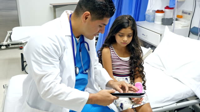 Pediatrician discussing care of injured arm with little girl