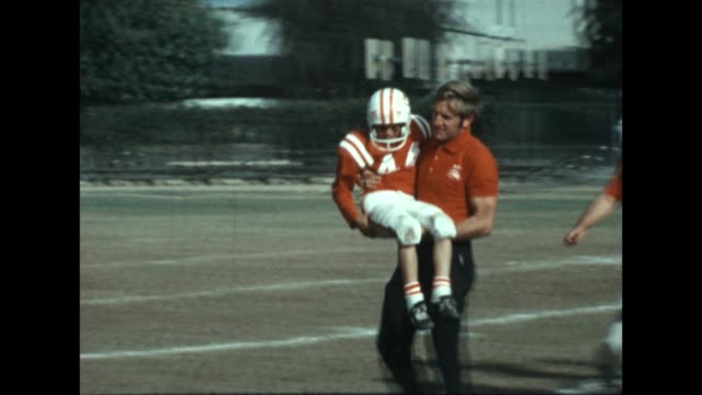 A Pee Wee League football player is carried from the field with an injury in the late 1960's