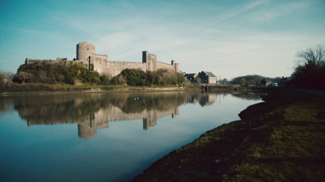 WS Pembroke Castle's reflection mirrored in surrounding moat / Pembroke, Wales, United Kingdom