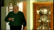 Pensioner making tea / woman feeding baby ENGLAND Kent Bromley EXT Alan Hone along into kitchen / set ups as makes cup of tea / Hone into living room...